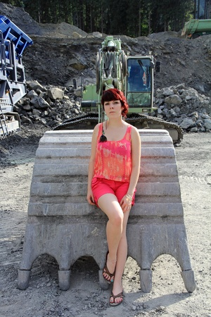 energetically: a young woman on the building site before the big excavator shovel Stock Photo