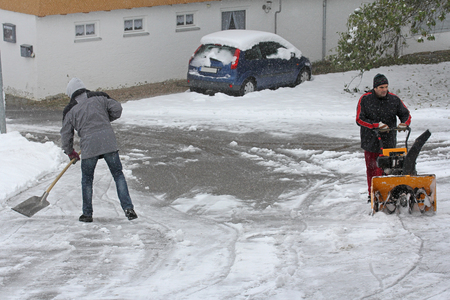 snow clearing: Two men clearing snow in winter Stock Photo