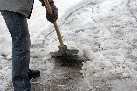 A man clears snow from the sidewalk Stock Photo