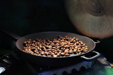 Chestnuts are roasted in a large skillet photo