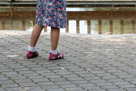 children s feet: A child stands in front of a rain puddle Stock Photo