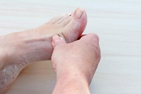 Een vrouw heeft pijn in de voet