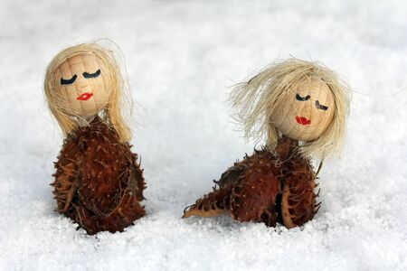 spat: Two small wooden figures in the snow Stock Photo