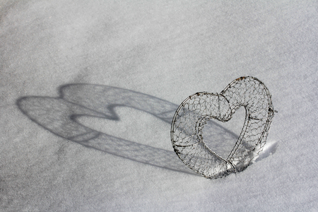 feel affection: A heart with shadow in the snow