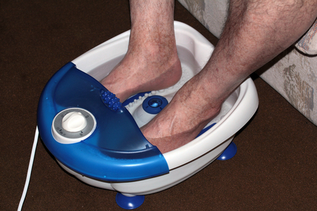Foot care through a footbath Фото со стока