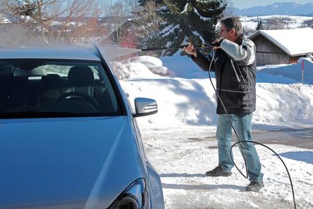 Een man wast een auto in de winter