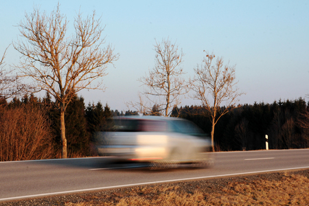 too fast: A car drives too fast. An excessive speed while driving increases the risk of accidents Stock Photo
