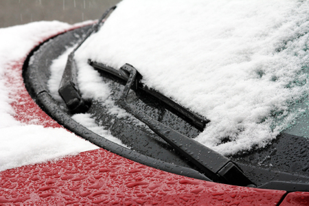 A snow-covered car. Winter and snow on the road Фото со стока