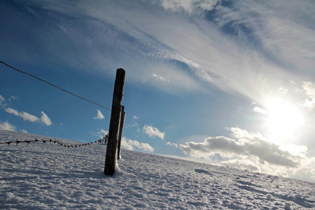 fence post: Barbed wire fence with fence post in the winter landscape. An icy winter landscape with fence posts Stock Photo