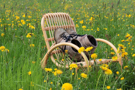 In spring, the season begins mountaineers, mountain boots on a rocking chair waiting photo