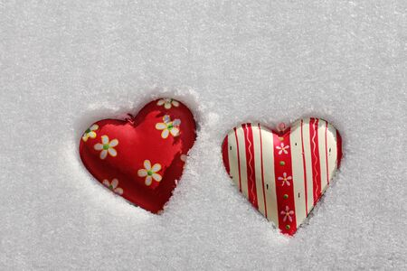 cordiality: Two red hearts in the snow. Two colorful heart lying in the snow Stock Photo