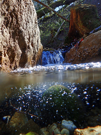 springwater: An underwater and water uptake by a stream. An underwater shot in a creek Stock Photo