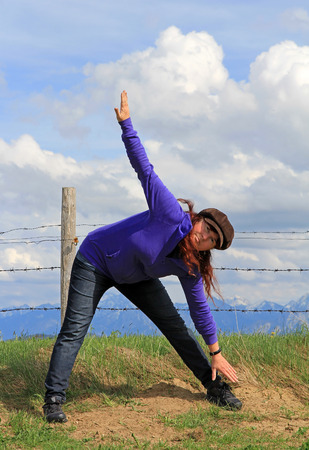 sporting activity: A woman doing gymnastics and stretching exercises in nature. Sporting activity in nature