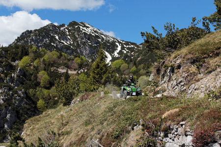 adventurous: Motorsport With the ATV in the mountains. Adventurous ride on a mountain pass Editorial