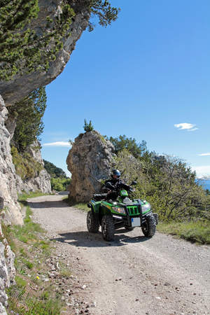 Motorsport With the ATV in the mountains. Adventurous ride on a mountain pass 스톡 콘텐츠