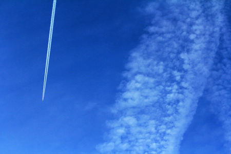 strips away: A plane with contrails in the blue sky