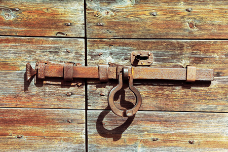 old wooden door: a door lock from metal on an old wooden door. Completed door Stock Photo