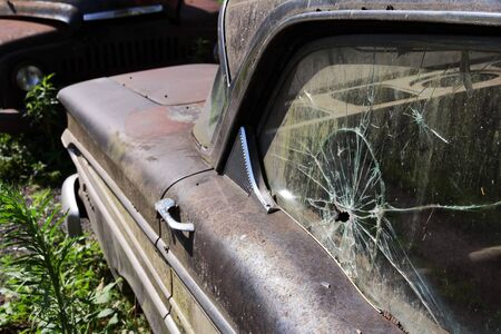 total loss: A broken side window in an old rusted car. A broken vintage