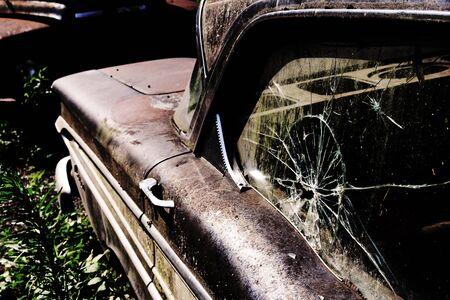 A broken side window in an old rusted car. A broken vintage