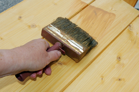 A woman sweeps with a brush Wood preservation glaze on boards Stock Photo