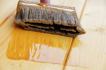Een borstel met houtconserveringsmiddel om de coating van hout te beschermen Stockfoto