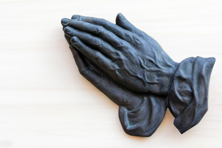 intercede: The praying hands of an old woman made of metal Stock Photo