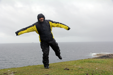 rainwear: A man in rain and storm. A very windy day on the beach