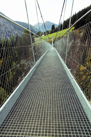 gratings: The long road over the bridge. The long suspension bridge in the mountains Stock Photo