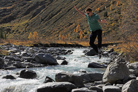 recreational climbing: A young man jumping over a rock by the river in the mountains. A mountain Hikers jumping