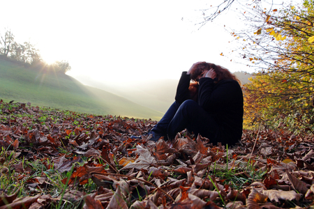 unmotivated: Depression in autumn - A sad woman sitting in foliage Stock Photo