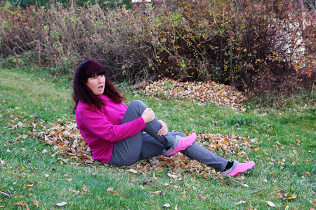 personal injury: Autumn - accident risk by slipping on wet leaves. A woman slipped on wet leaves