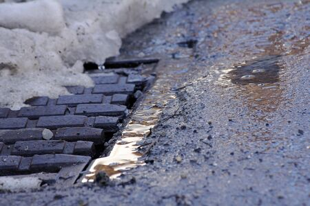 manhole cover: Winter - A wet frozen ground in front of a manhole cover