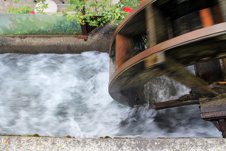 watermills: The wheel of a water mill in South Tyrol - An ongoing water mill beside a stream Stock Photo