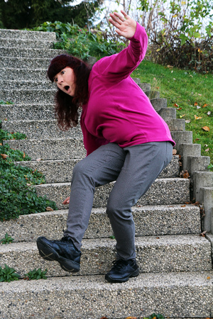 personal injury: Danger of crash and risk of accidents on stairs - A woman stumbles on a staircase