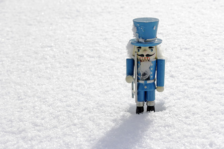 cilinder: A blue wooden nutcracker in the snow