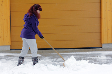 Snow removal in winter - A woman admits snow in front of a garage