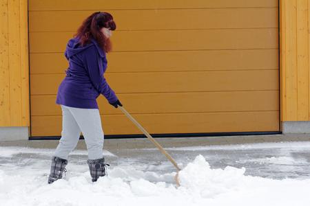 Sneeuwruimen in de winter - Een vrouw geeft toe sneeuw in de voorkant van een garage Stockfoto