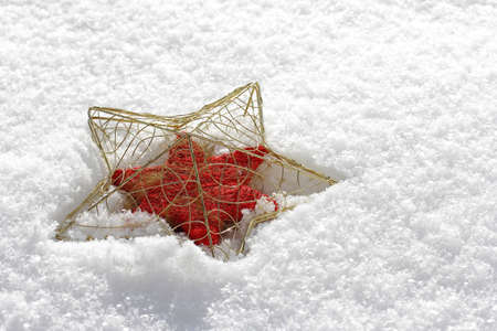 gold christmas: A gold-red Christmas star in snow Stock Photo