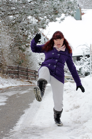 Risk of accidents in winter - A woman slips on a slippery road snow Standard-Bild
