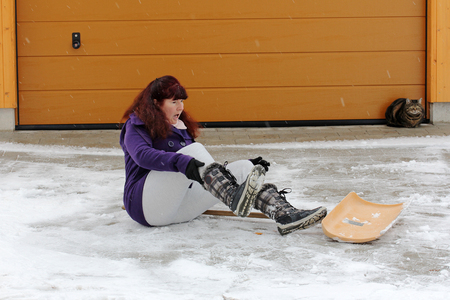 personal injury: Accident risk When clearing snow. A woman slipped shoveling snow Stock Photo