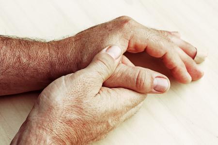 Een bejaarde man heeft pijn in de vingers en handen