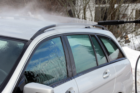 rinse spray hose: Car wash in the winter - rinsing of salt and dirt Stock Photo