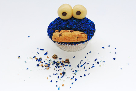 Een grappige muffin met ogen, mond en blauwe sprinkles
