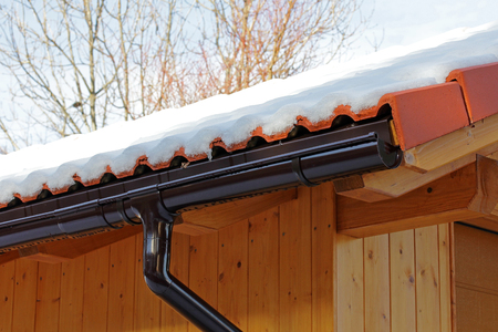 A wooden roof with rain gutter and drainpipe in winter