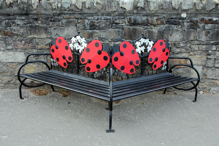 exceptionally: A bench of metal with red ladybirds Stock Photo