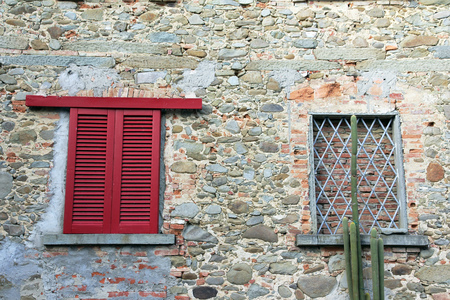 gratings: A window with closed red shutters and a bricked, barred window on a wall