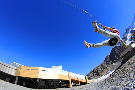 sportsmanship: A young woman slips on a zipline in the mountains