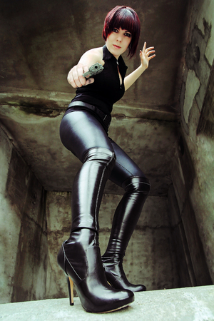 A young woman in black clothes and high boots in action Stock Photo