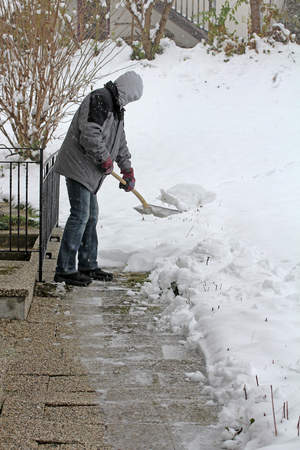 A man clears snow in winter from a footpath