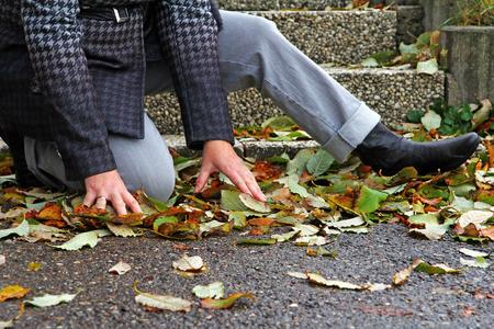 Natte en gladde straten kan leiden tot ongelukken. Een vrouw is uitgegleden op natte bladeren Stockfoto